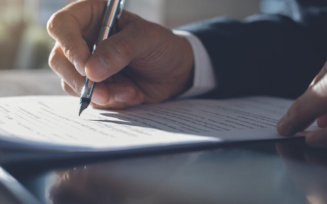 Een hand dat een vulpen vast heeft en schrijft iets op papier.