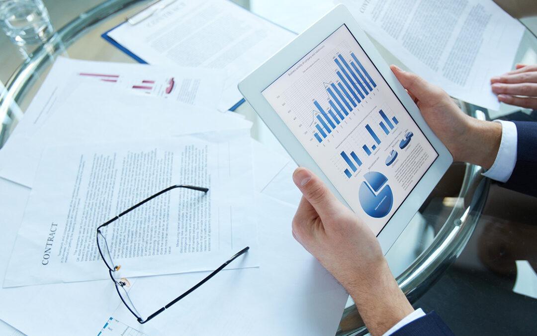 Een witte tablet, in de handen van een man, met daarop grafieken te zien. De man zit aan een glazen tafel, met daarop papieren verspreid en een bril.