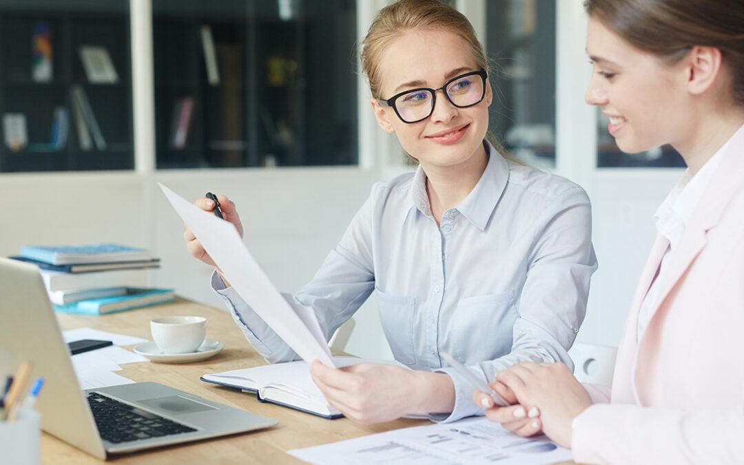 Vrouw met bril, die het contractmanagementsysteem toont aan een andere vrouw uitlegt. Ze zitten aan een tafel met daarop een kopje, computer en een stapel boeken.